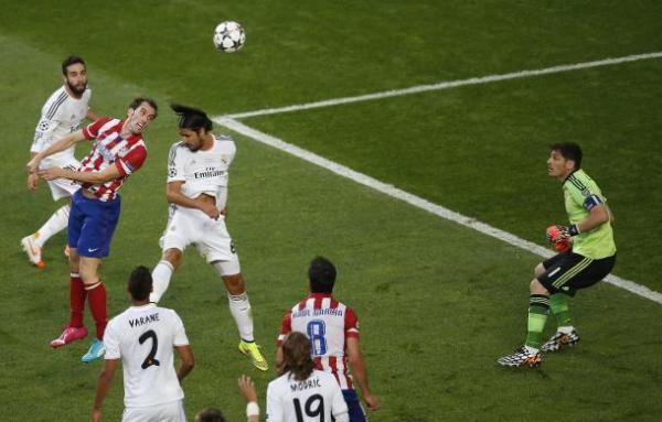 Atletico Madrid's Godin heads the ball to score a goal against Real Madrid during their Champions League final soccer match at the Luz Stadium in Lisbon