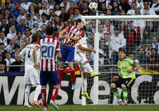 Atletico Madrid's Godin jumps and shoots the first goal for the team during their Champions League final soccer match against Real Madrid at the Luz Stadium in Lisbon