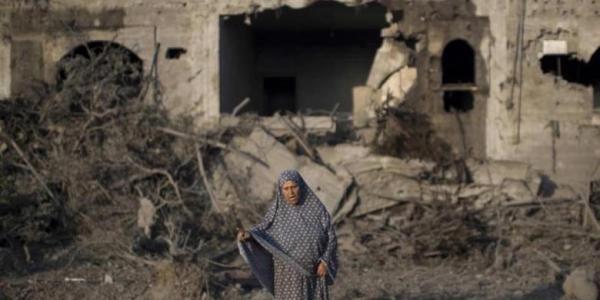 Seorang wanita Palestina berdiri di tengah puing-puing gedung yang hancur akibat serangan udara Israel ke kota Gaza, 8 Juli 2014. Puluhan warga Palestina termasuk wanita dan anak-anak turut menjadi korban dalam serangan tersebut